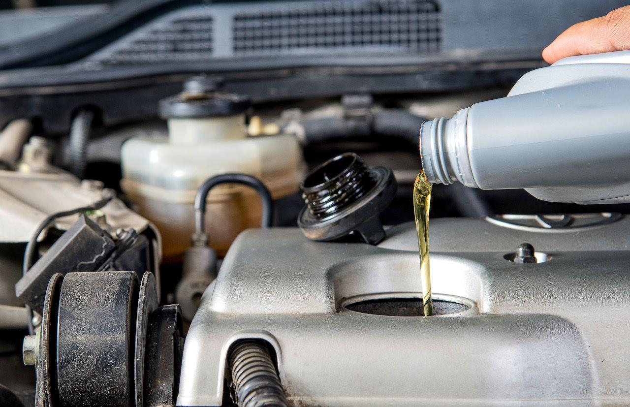 Öl wird aus Behälter in Motor gekippt