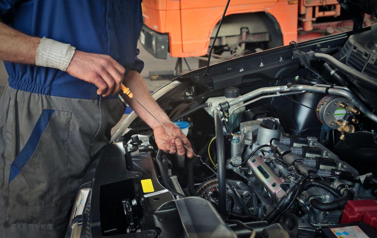 Mechaniker misst Ölstand am Auto