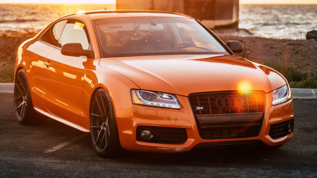 Orangener Audi steht auf einem Parkplatz bei Sonnenuntergang