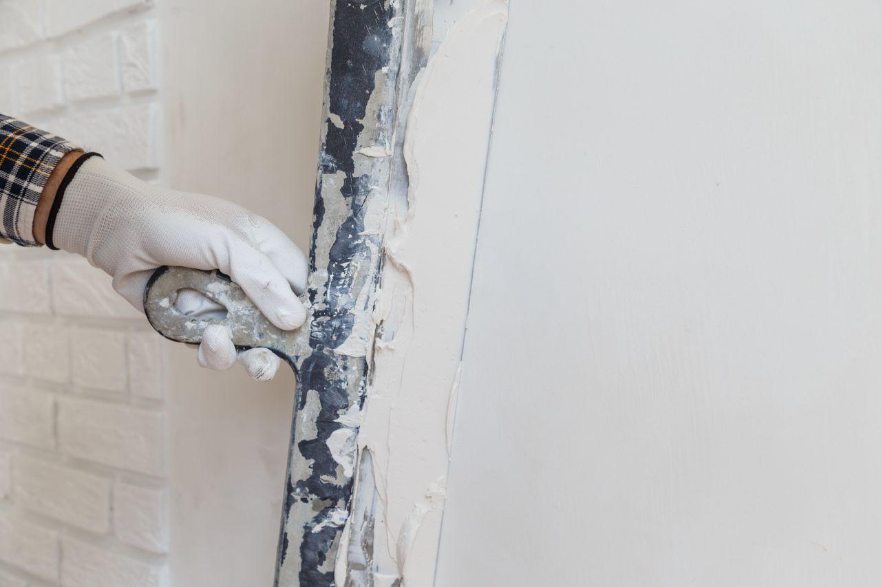 Maler schmiert Paste an die Wand